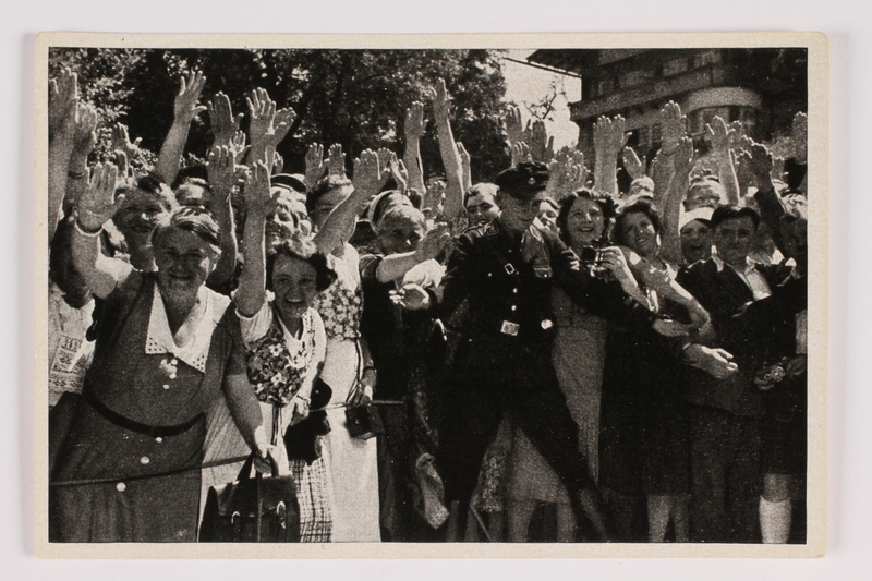 2012.68.12 front Cigarette card photo of happy women in folk costume giving Heil Hitler salute