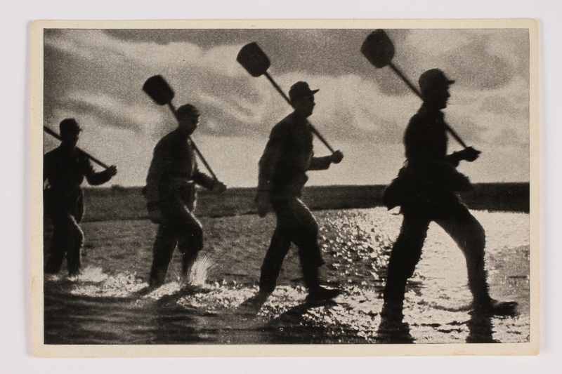 2012.68.13 front Cigarette card photo of 4 workers carrying shovels on their shoulders