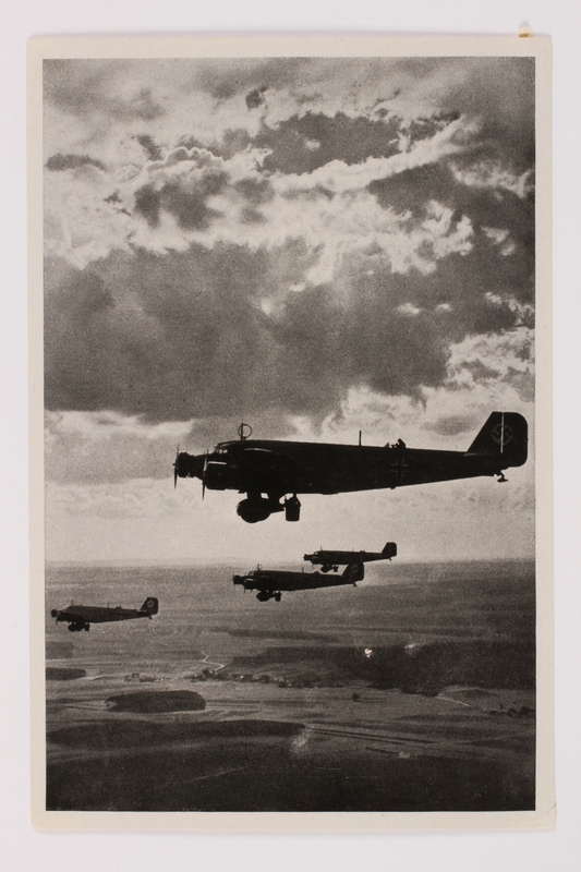 2012.68.14 front Cigarette card photo of four bomber planes flying over Nuremberg