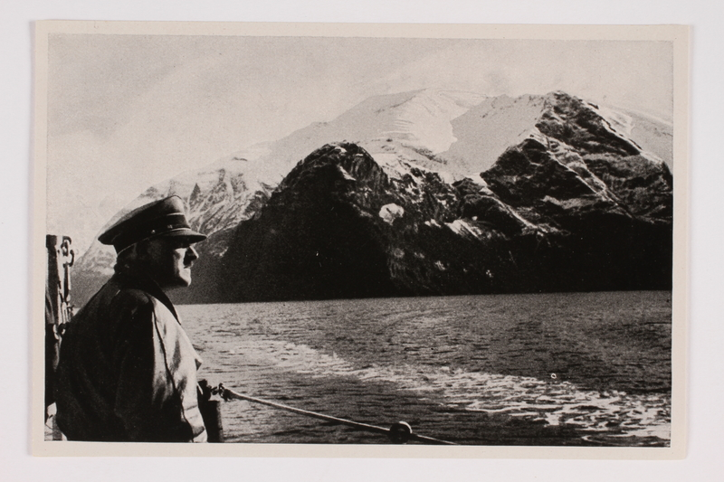 2012.68.15 front Cigarette card photo of Hitler on a warship gazing across a fjord