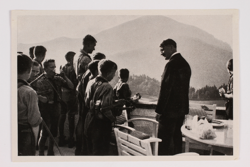 2012.68.16 front Cigarette card photo of Hitler chatting with a Hitler Youth group