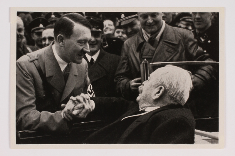 2012.68.17 front Cigarette card photo of Adolf Hitler visting General Litzmann on his birthday