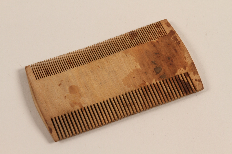 2012.310.1_a front Wooden comb and handmade paper case given to a prisoner by a friend in Kaiserwald concentration camp