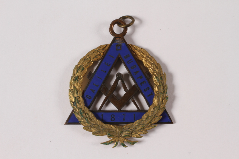 2010.81.9 front Gold and blue enamel Masonic medal with the compass and square emblem owned by a Jewish Hungarian emigre