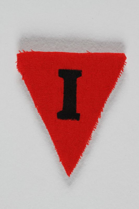 1991.198.10 front Unused red triangle concentration camp prisoner patch with a black letter I found by US forces