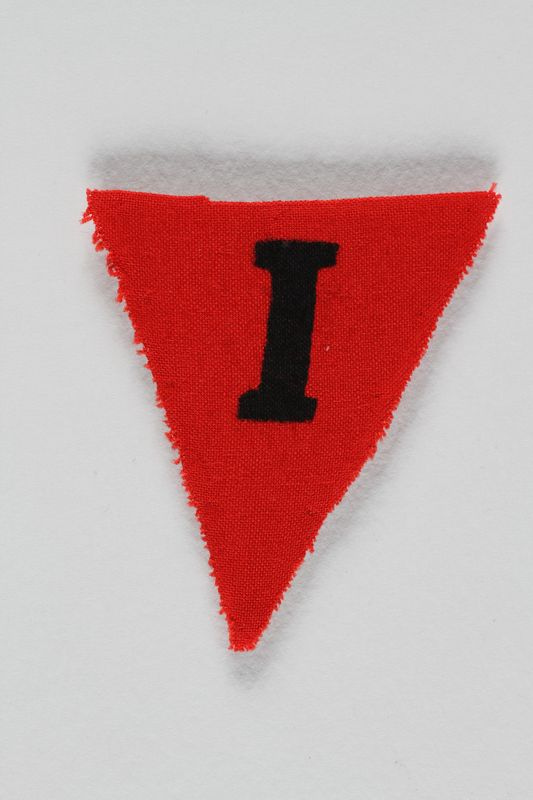 1991.198.11 front Unused red triangle concentration camp prisoner patch with a black letter I found by US forces