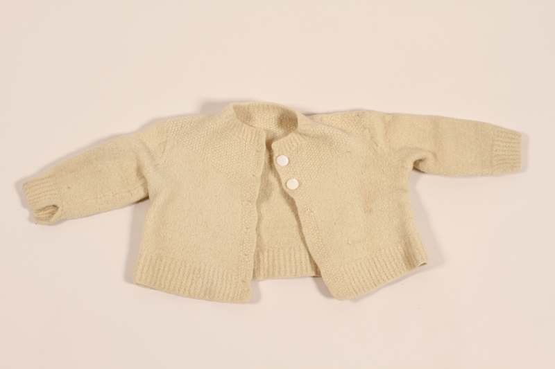 2012.242.3 front Infant's wool knit sweater with white buttons made for a baby by his mother while in hiding