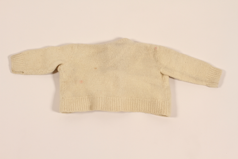 2012.242.3 back Infant's wool knit sweater with white buttons made for a baby by his mother while in hiding
