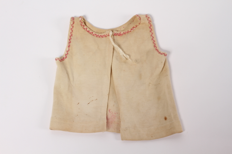 2012.242.5 front Infant's vest with decorative pink stitches made for a baby by his mother while in hiding