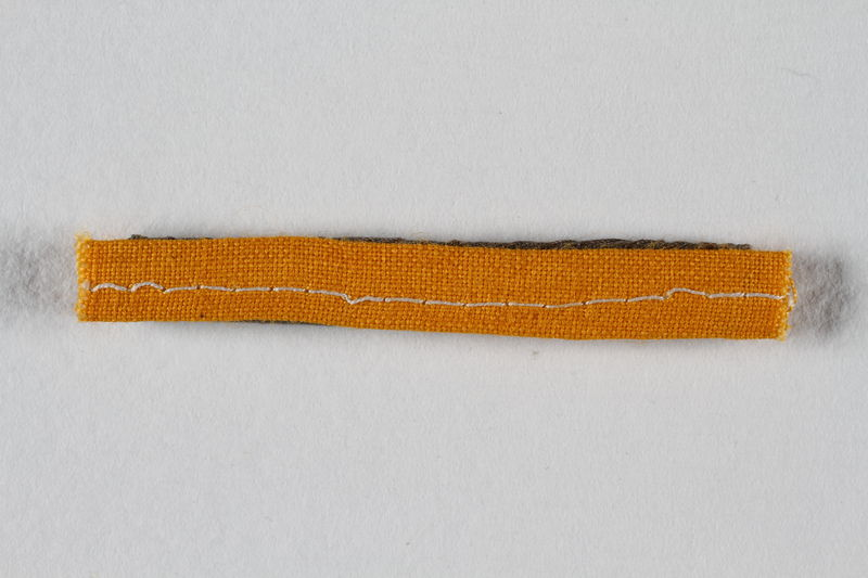 1991.198.4 front Unused yellow stripe concentration camp prisoner patch found by US forces