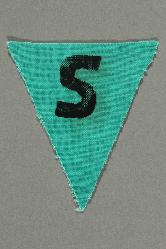 1991.198.6 front Unused green triangle concentration camp prisoner patch with a black letter S found by US forces