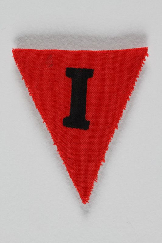 1991.198.9 front Unused red triangle concentration camp prisoner patch with a black letter I found by US forces