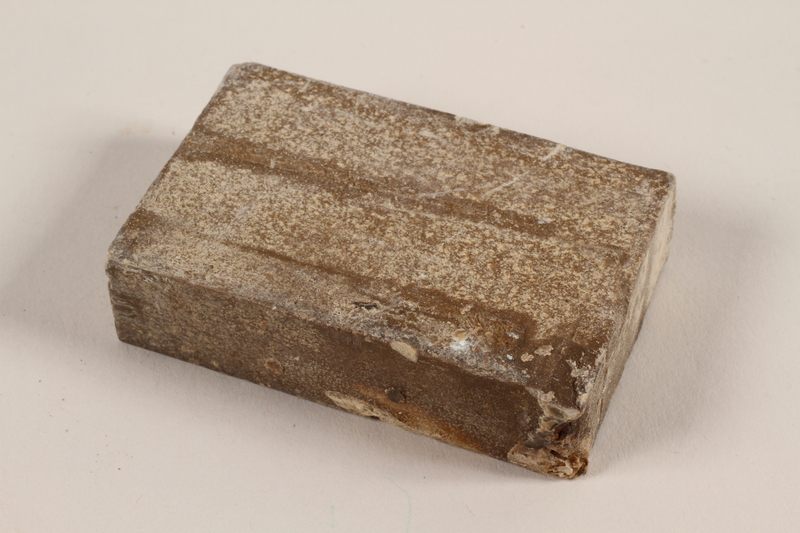 1991.215.1 front Unused brown soap bar with broken corner imprinted RIF 0667