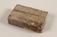 1991.215.1 front Unused brown soap bar with broken corner imprinted RIF 0667  Click to enlarge