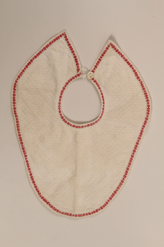 2011.424.4 front White baby's bib with red trim worn by a Jewish infant while living in hiding
