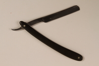 2010.240.5 open Straight razor in a black plastic cover brought to Shanghai by an Austrian Jewish refugee  Click to enlarge