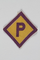2001.204.2 front Forced labor badge, yellow with a purple P, to identify a Polish forced laborer  Click to enlarge