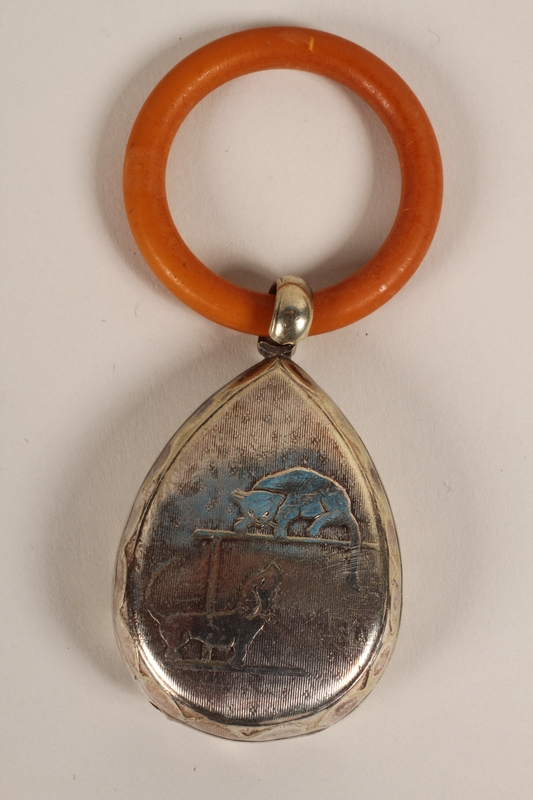 2012.355.2 front Silver and plastic teething ring rattle used by an infant who was placed in hiding by his family
