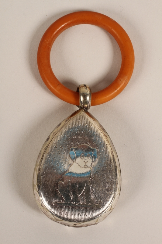 2012.355.2 back Silver and plastic teething ring rattle used by an infant who was placed in hiding by his family