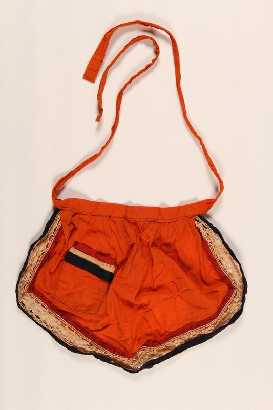 2002.139.2 front Orange and blue apron made for a hidden Dutch Jewish child
