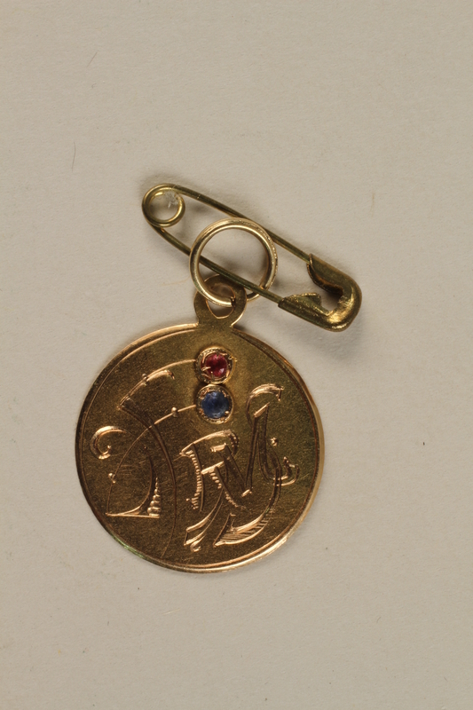 2003.32.1 front Gold pendant with the initials of a girl and her parents from her aunt