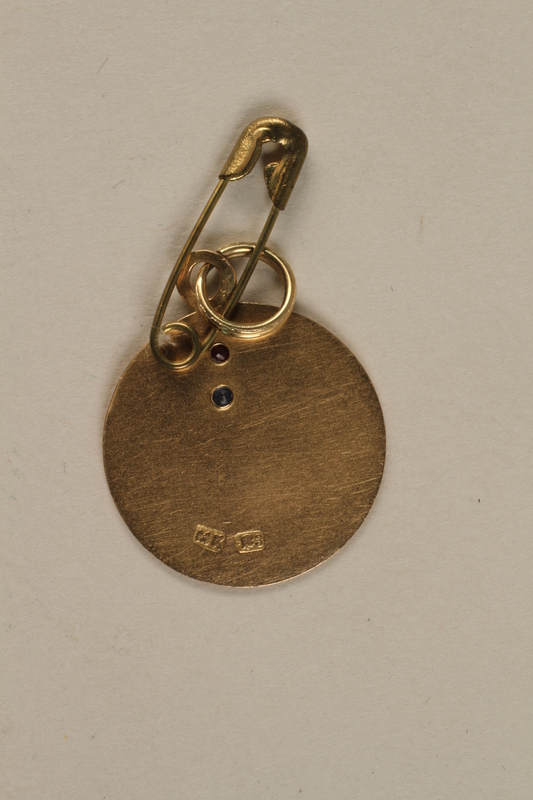 2003.32.1 back Gold pendant with the initials of a girl and her parents from her aunt