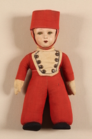2002.371.2 front Doll in a red hat and uniform kept by a young girl while living in hiding  Click to enlarge
