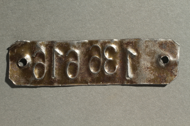 2002.446.1 back Metal tag with her stamped prisoner number worn as a bracelet by a concentration camp inmate
