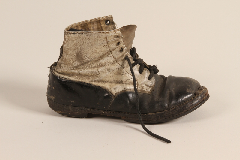 2002.447.1 a front Pair of toddler's well used black and white leather lace-up boots worn in Theresienstadt ghetto/labor camp