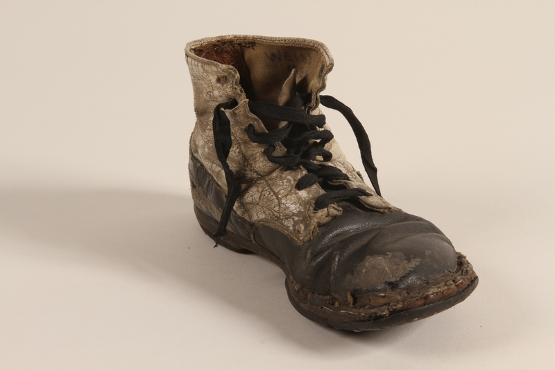 2002.447.1 b front Pair of toddler's well used black and white leather lace-up boots worn in Theresienstadt ghetto/labor camp