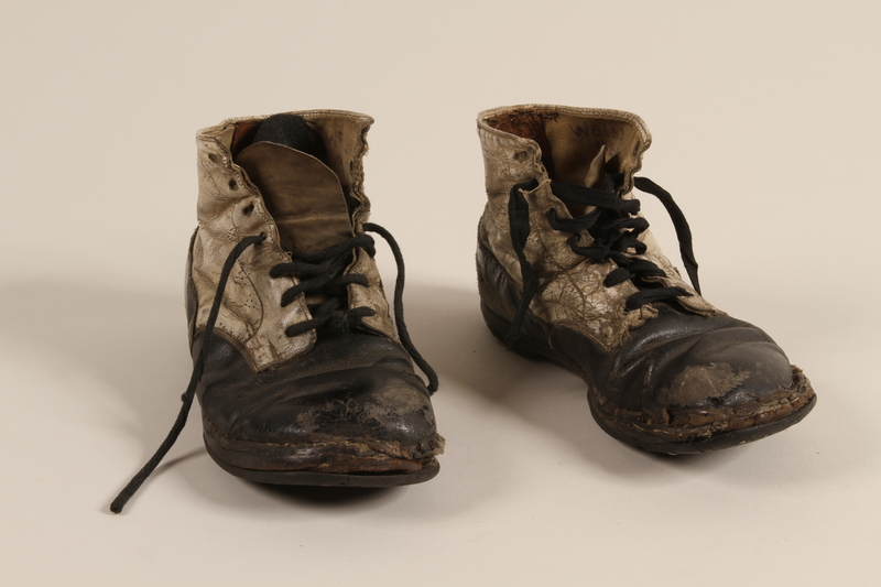 2002.447.1 a-b front Pair of toddler's well used black and white leather lace-up boots worn in Theresienstadt ghetto/labor camp
