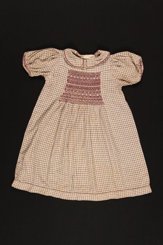 2003.200.1 front Red checked dress with smocking made for a young Jewish girl who escaped Germany on the Kindertransport