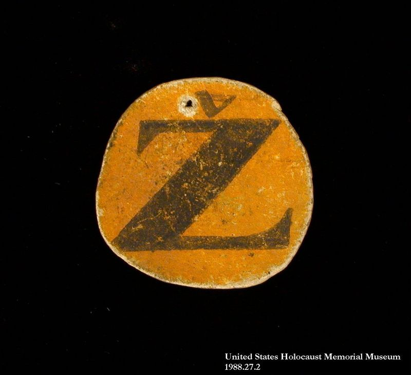 1988.27.2 front Yellow cardboard badge with Croatian Z for Jew worn by a Sephardic Jewish man