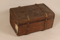 2003.242.3 back Square, brown burlap covered trunk used postwar by a young German Jewish refugee  Click to enlarge