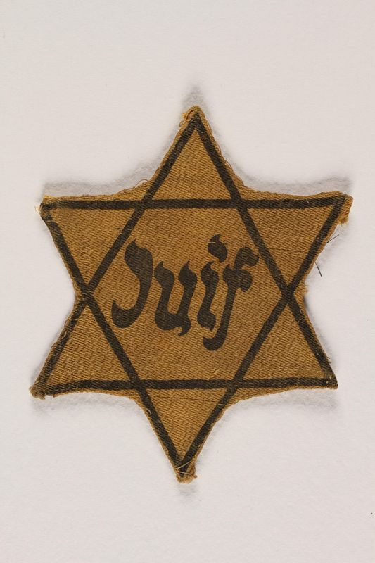 2003.357.1 front Factory-printed Star of David badge printed with Juif, acquired by a Jewish Lithuanian artist