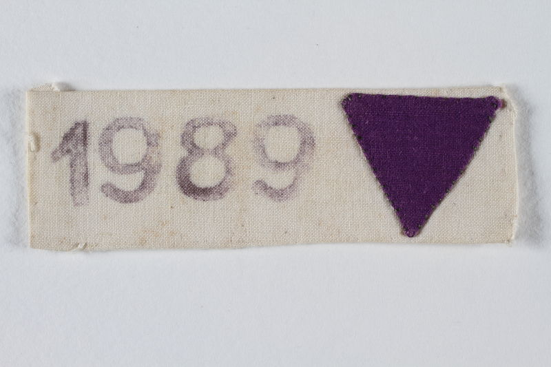 1989.240.2 front White inverted triangle patch and prison number worn to identify a female inmate as a Jehovah's Witness