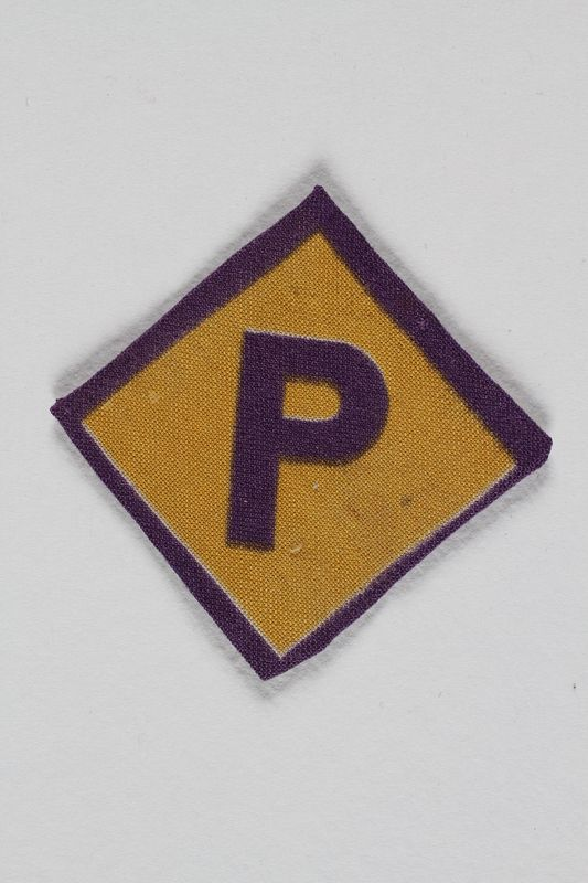 1989.285.2 front Forced labor badge, yellow with a purple P, worn by a Polish Jewish woman in hiding as a Catholic