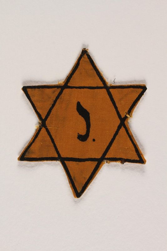 2003.348.2 front Yellow Star of David badge with the letter J worn by a Belgian Jewish boy