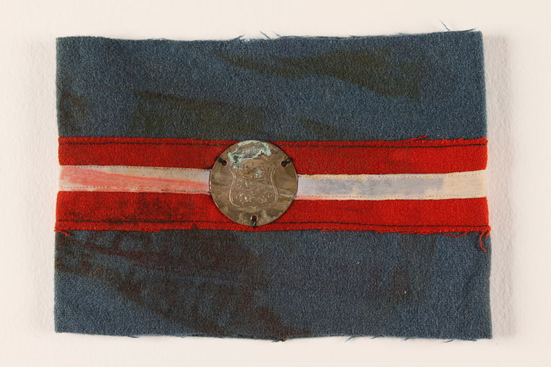1989.297.4 front Blue armband with a royal coat of arms medallion issued to a Danish resistance fighter