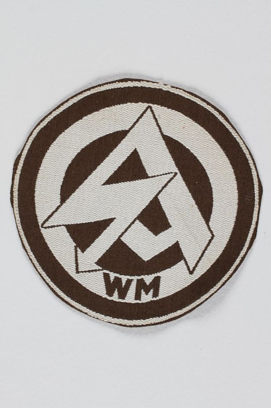 1989.312.35 front SA sport club patch with a WM monogram and stylized arrow symbol