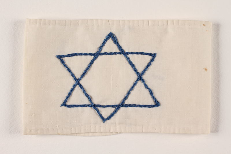 1990.51.3 front White armband with a blue embroidered Star of David worn by a Polish Jewish youth