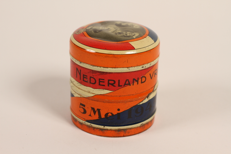 2003.419.1_a front Orange decorated candy tin with lid distributed on the liberation of the Netherlands received by a former hidden child
