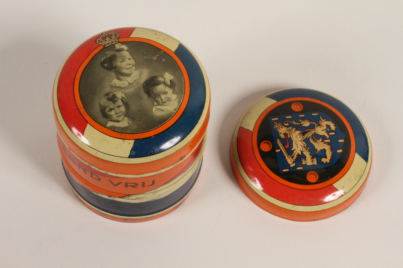 2003.419.1_a-b front Orange decorated candy tin with lid distributed on the liberation of the Netherlands received by a former hidden child