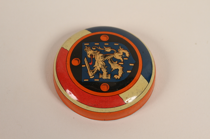 2003.419.1_b front Orange decorated candy tin with lid distributed on the liberation of the Netherlands received by a former hidden child