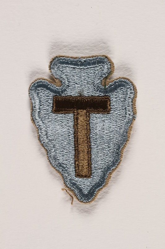 2000.561.3 front US Army 36th Infantry Division shoulder sleeve patch with a T monogram on a light blue field