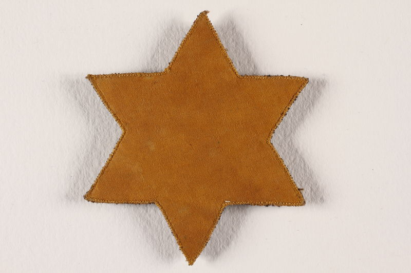 2004.36.2 front Yellow Star of David badge with tweed backing worn in Slovakia