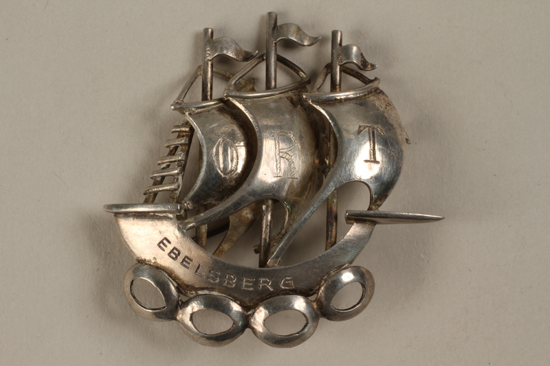1988.72.23 front Silver brooch of a 3 masted ship given to Director, ORT schools, DP camps