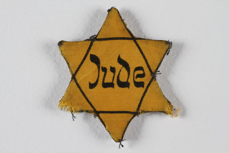 1988.82.1 front Yellow cloth Star of David badge printed with the word Jude