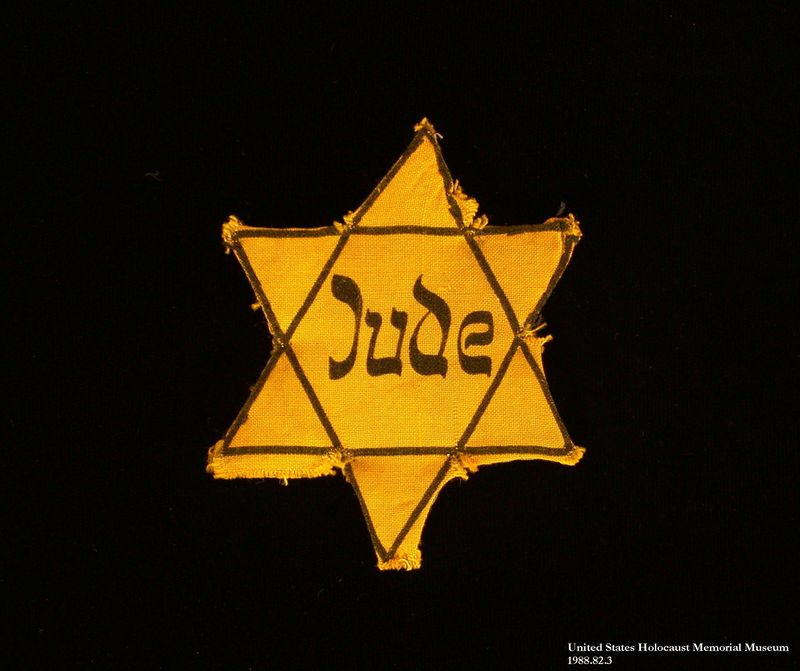 1988.82.2 front Yellow cloth Star of David badge printed with the word Jude