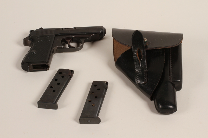 1988.112.65_a-d front Semi-automatic Walther PPK pistol, holster, and magazines found at a concentration camp by US military aid worker